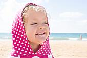 Girl wearing hood with polka dots at beach