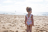 Little girl staring at the sea