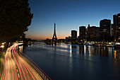 Light trails on a street along the River Seine at twilight, Paris, France
