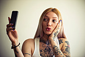 Tattooed woman taking selfie with smartphone