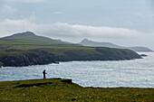 Ein Wanderer genießt eine Momente Pause, um die atemberaubende Aussicht von den Klippen entlang der Pembrokeshire Küstenpfad, Wales, Vereinigtes Königreich, Europa zu bewundern