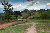 A mini bus drives along a red dusty earth road through rural Uganda, Africa