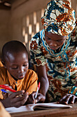 A teacher helping a young student at a school, Ghana, West Africa, Africa
