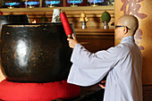 Vietnamese Buddhist nun using a giant singing bowl, Vung Tau, Vietnam, Indochina, Southeast Asia, Asia