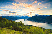 Lake Como surrounded by green meadows framed by pink sky at dawn, Cremia, San Domenico, Lombardy, Italian Lakes, Italy, Europe