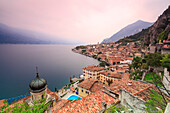 Pink sunrise lights up Lake Garda and the typical town of Limone Sul Garda, province of Brescia, Italian Lakes, Lombardy, Italy, Europe