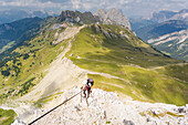 a hiker is climbing a very hard via ferrata, Trento province, Trentino Alto Adige, Italy