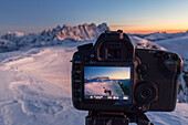Europe, Italy, Veneto, Belluno, A SLR camera in mountain with live view display active frames the mountains in background