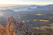 Hikers sitting on the top of Pulpito di Cima Popa - Poppekanzel at sunset looking to the horizon, Latemar, Bolzano, South Tyrol, Dolomites, Italy