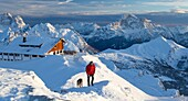 Hiker with german shepherd on the snowy crest surrounded by the high peak of Monte Civetta Dolomites Belluno province Veneto Italy Europe