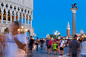 Tourists admire the historical buildings at dusk in St Mark's Square Venice Veneto italy Europe