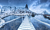 A bridge over the cold sea connects a typical fishing village, Lofoten Islands Northern Norway Europe