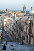 Tourists on flight of steps admire the old town and dome of cathedral of Caltagirone province of Catania Sicily Italy Europe