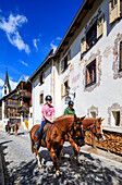 Horse riding in the old alleys of the alpine village Guarda canton of Graubünden Inn District Lower Engadine Switzerland Europe