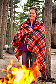 A woman smiles while she stands next to a campfire with a plaid wool blanket wrapped around her.