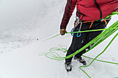 Ice climber belaying partner up to the belay