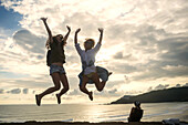 Young women jumping with arms raised on coastline