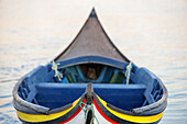 Traditional moliceiro fishing boat with a high prow, painted in vivid colours and with distinctive patterns.