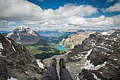Low section of hiker sitting on Mount Tuzo, Banff, Alberta, Canada