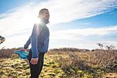 Frau Strethcin für eine Trail-Lauf auf einem Küstenweg in Newport, Rhode Island, während des Frühlings