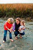 Woman kneeling with her daughter in arm in marsh, Wrightsville Beach, North Carolina, USA