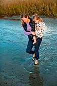 Eine Frau geht durch seichtes Wasser und trägt ihre Tochter in ihren Armen in einem Sumpf in Wrightsville Beach, North Carolina.