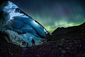 Majestic scenery with Aurora Borealis over glacier and man at night in Jasper National Park, Alberta, Canada