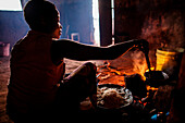 Ester Hodari, age 22 years old, cooks dinner using the traditional three-rock cook stove with a fire in the middle. These cookstoves use a lot of fuel, firewood, and produce a lot of smoke. Ester told us that cooking with this type of stove made her eyes