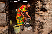 Solar Sister entrepreneur Julieth Mollel, 61, prepares to cook dinner on her clean cookstove at her home near Arusha, Tanzania.                                                   Julieth Mollel stands tall when she says she is a Solar Sister Entrepreneur a