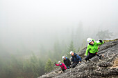 A women takes  selfie with a group of people who are enjoying a Via Ferrata in Squamish, British Columbia.