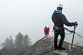 A man waits and looks back as a women climbs up the metal rungs of a Via Ferrata in Squamish, British Columbia.