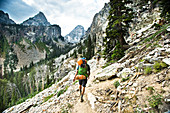 A Backpacker Hiking Through Rocky Terrain In Jackson Hole, Wyoming