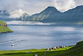 Hellur located at fjord Oyndarfjordur, in the background the mountains of the island Kalsoy. The island Eysturoy one of the two large islands of the Faroe Islands in the North Atlantic. Europe, Northern Europe, Denmark, Faroe Islands.