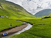 Village Elduvik located at fjord Funningsfjordur. The island Eysturoy one of the two large islands of the Faroe Islands in the North Atlantic. Europe, Northern Europe, Denmark, Faroe Islands.