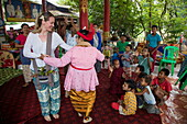 Guest of Ayeyarwady (Irrawaddy) river cruise ship Anawrahta (Heritage Line) dances with locals woman during cultural performance in village, Tagaung, Mandalay, Myanmar