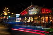 Light streaks of car passing A Little Bit of Bagan restaurant and bar at night, Nyaung-U, near Bagan, Mandalay, Myanmar