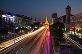 Streaks of car lights on Sule Pagoda Road and illuminated Sule Pagoda at dusk, Yangon, Yangon, Myanmar