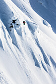 Berufssnowboarder Helen Schettini, fängt Luft und ergreift ihr Brett an einem sonnigen Tag beim Snowboarding in Haines, Alaska.