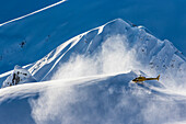 A helicopter used to carry skiers and snowboarders to the top of mountains takes off and blows snow in the air on a sunny choking day in Haines, Alaska.