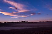 Airplane flies over mountain range in Nevada desert against sky at dusk