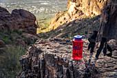 Rote Wasserflasche mit zwei Wanderstöcken auf Felsen, Aberglaube-Berge, Arizona, USA