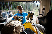 A climber packs mountaineering shoes and climbing shoes in preparation for an expedition