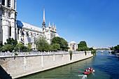 France, Paris, 4th arrondissement, Ile de la Cite, Notre-Dame Cathedral. Recreational boat sailing on the Seine.