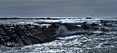 France, panoramic view of a stormy sea crossing a rock slant. Lighthouse right background