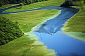 Montenegro, Boat sailing at high speed in meander of the river Crnojevica, streaming of the lake Skadar