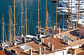 France, Southern France, Cannes, Mast of large sailboats in the port of Cannes and red roofs of houses