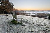 Holzbank und Blick über Sussex Landschaft bei Sonnenaufgang im Frost, Burwash, East Sussex, England, Vereinigtes Königreich, Europa