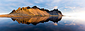 Panoramic view of mountains of Vestrahorn and perfect reflection in shallow water, soon after sunrise, Stokksnes, South Iceland, Polar Regions