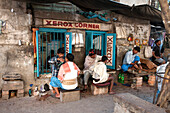 Barbers cutting hair and shaving men, and tobacco wallah, in street stalls outside Xerox shop in Dalhousie Square area of Kolkata ,Calcutta, West Bengal, India, Asia