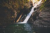 Man rappelling off waterfall while canyoneering in Deneau Creek, Hope, British Columbia, Canada